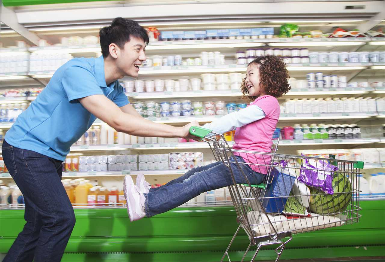 Parent pushing daughter in grocery cart in asian super market